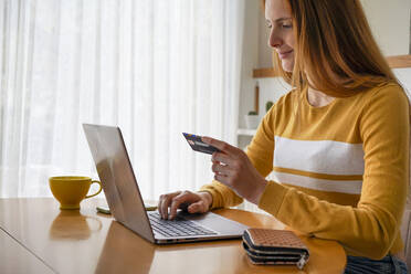 Young woman with credit card using laptop at home - AFVF05825