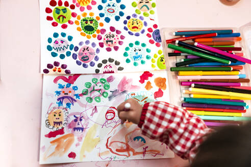 Little girl drawing  ugly viruses with color markers at home - GEMF03505