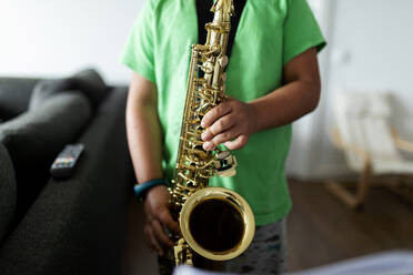 Boy exercising to play the saxophone at home - VABF02679