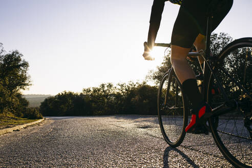Close-up of athlete riding bicycle on country road at sunset - ABZF03075