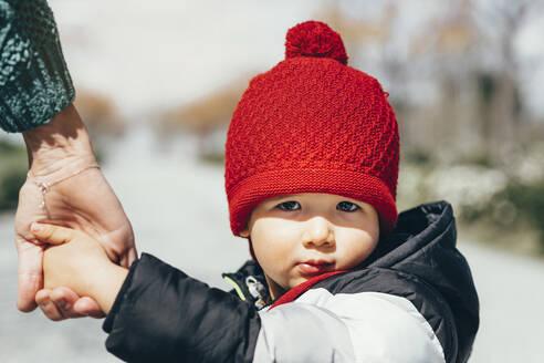 Portrait of little boy wearing red bobble hat - JCMF00440