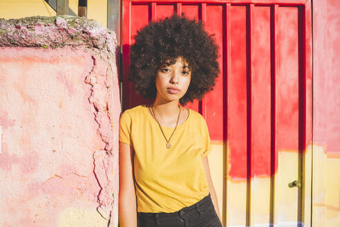 Portrait of young woman with afro hairdo leaning against a wall - MEUF00220