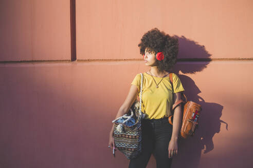 Young woman with afro hairdo listening to music with headphones - MEUF00235