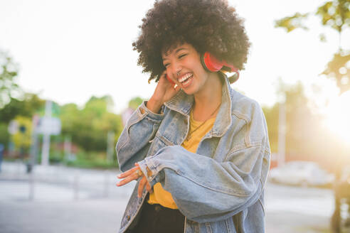 Happy young woman with afro hairdo dancing in the city - MEUF00244