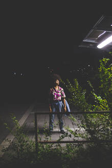 Young woman with afro hairdo standing on platform at night - MEUF00274