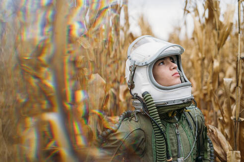 Young spaceman standing in wilted corn field - JCMF00451