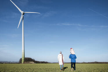 Back view of parents with little daughter walking on a field with wind wheel in the background - VYF00068