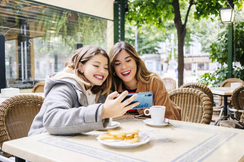 Two happy young women taking a selfie at an outdoor cafe - DGOF00557