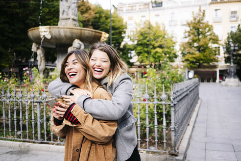 Two happy young women hugging in the city - DGOF00563