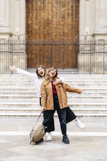 Two happy young women posing in the city - DGOF00569