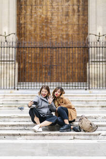 Two happy young women sitting on stairs in the city taking a selfie - DGOF00572