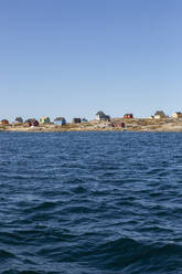Houses on sunny remote ocean coastline Disko Bay West Greenland - HOXF05789