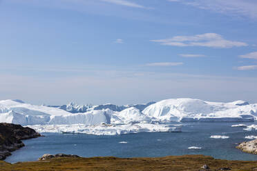 Majestic glacial icebergs on sunny remote Atlantic Ocean Greenland - HOXF05801