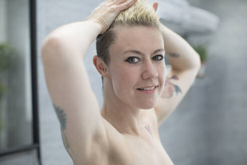 Portrait confident beautiful woman with tattoos in bathroom - HOXF06041