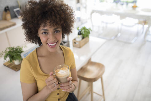 Portrait happy young woman drinking cappuccino in kitchen - HOXF06068