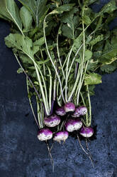 High angle close up of a bunch of freshly picked pink turnips on grey background. - MINF14423