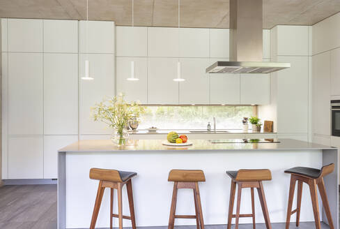 Modern white kitchen with island and barstools - CAIF24693