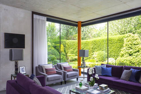 Modern living room with purple furniture and view of sunny garden - CAIF24696