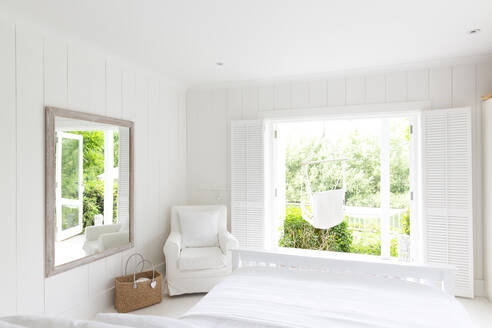 White, tranquil home showcase bedroom open to sunny patio with hammock - CAIF24729