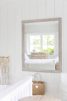 Reflection in mirror of white home showcase bedroom - CAIF24732