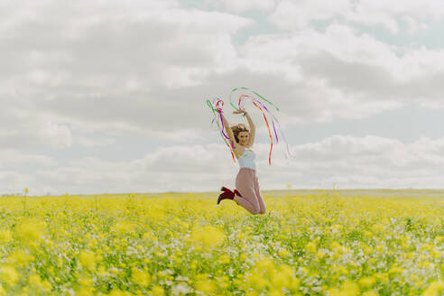 Happy young woman jumping with colourful ribbons in a flower meadow in spring - ERRF02876