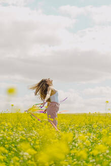 Happy young woman moving with colourful ribbons in a flower meadow in spring - ERRF02882