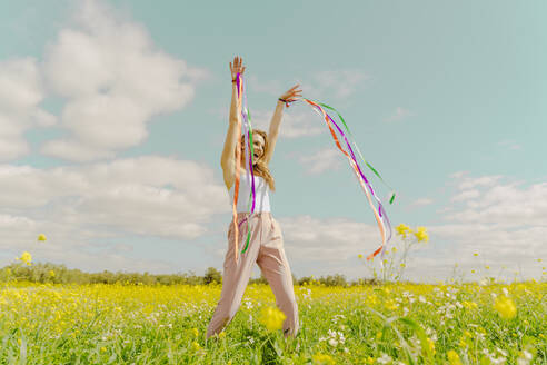 Happy young woman moving with colourful ribbons in a flower meadow in spring - ERRF02885