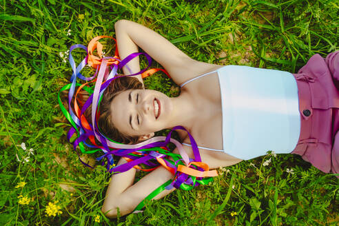 Happy young woman with colourful ribbons lying in a meadow - ERRF02897