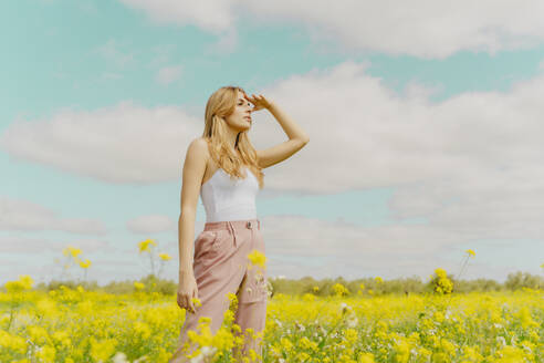 Young woman standing in a flower meadow in spring looking out - ERRF02903