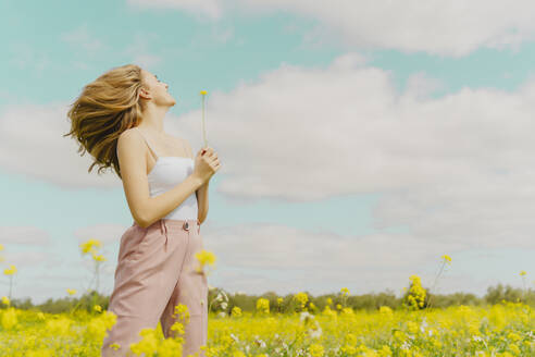 Happy young woman standing in a meadow in spring holding a flower - ERRF02906