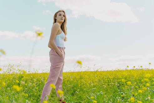 Young woman standing in a flower meadow in spring - ERRF02915