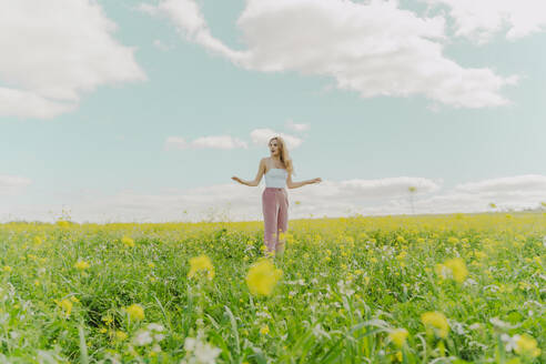 Young woman standing in a flower meadow in spring - ERRF02918