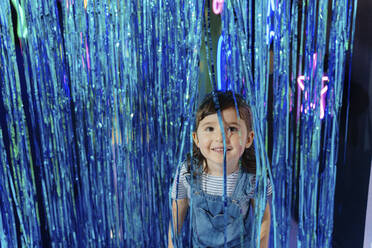 Portrait of smiling little girl among blue metallic curtain in a party room - GEMF03509