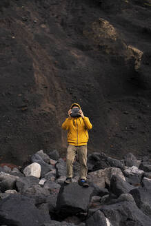 Man standing amidst volcanic rocks covering his face, Sao Miguel Island, Azores, Portugal - AFVF05832