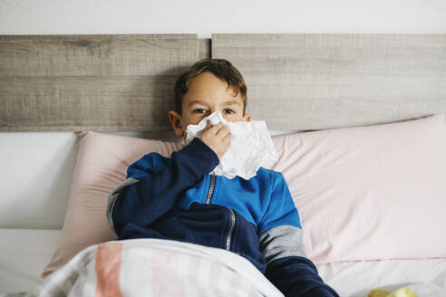 Portrait of sick boy lying in bed blowing nose - JRFF04248