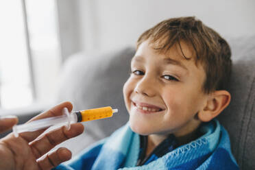 Portrait of grinning sick boy sitting on couch while his mother giving him medication - JRFF04260