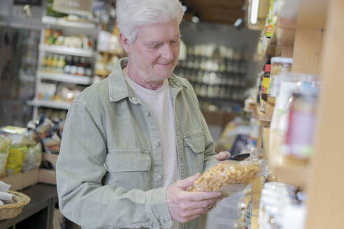 Senior man buying groceries in a small food store - AFVF05848
