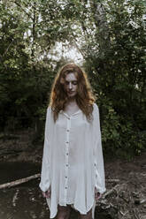 Young redhaired woman wearing baggy shirt in forest - AFVF05920