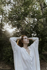 Young redhaired woman wearing baggy shirt in forest - AFVF05923