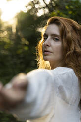 Young red-haired woman reaching out her hands in the forest - AFVF05926