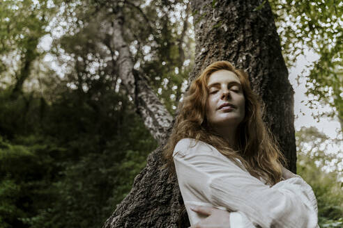 Young redhaired woman with closed eyes leaning on tree trunk - AFVF05929