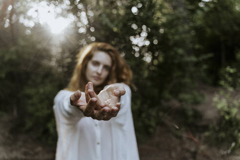 Young red-haired woman reaching out her hands in the forest - AFVF05932