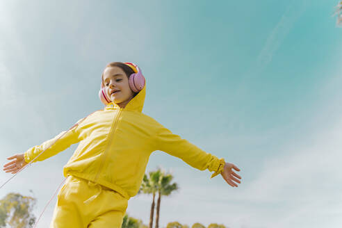 Portrait of little girl dancing while listening music with headphones - ERRF02949