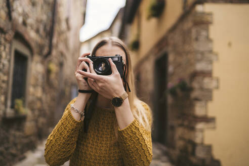 Young woman taking a picture with old-fashioned camera in old town, Greve in Chianti, Tuscany, Italy - JPIF00565