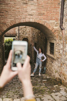 Woman taking a picture of her friend in picturesque old town, Greve in Chianti, Tuscany, Italy - JPIF00571