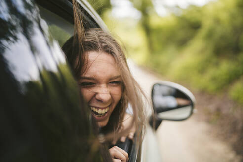 Carefree young woman leaning out of car window - JPIF00577