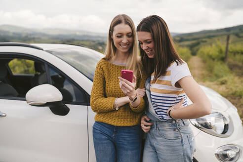 Two happy young women standing beside car sharing cell phone - JPIF00583