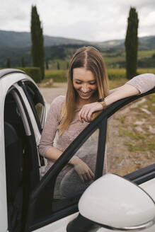 Happy young woman getting at a car in rural landscape, Tuscany, Italy - JPIF00586