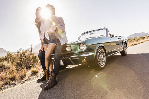 Couple embracing at convertible car on a country road in backlight - SDAHF00698