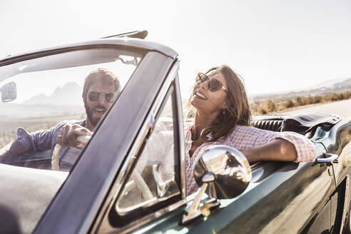 Happy couple in convertible car on a road trip - SDAHF00704